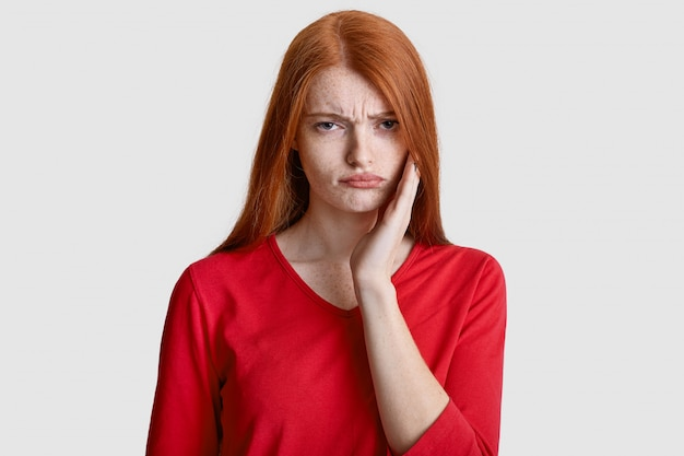 Displeased red haired woman with freckled skin, keeps hand on cheek, suffers from toothache, has sensitivity, wears casual red clothes, isolated on white. dental problems concept
