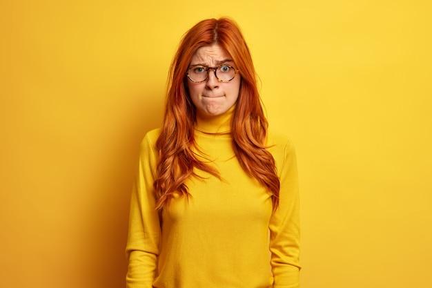 불쾌한 빨간 머리 유럽 여성이 입술을 누르고 긴장된 표정이 둥근 안경을 쓰고 캐주얼 폴로 넥이 몇 가지 문제에 직면합니다.