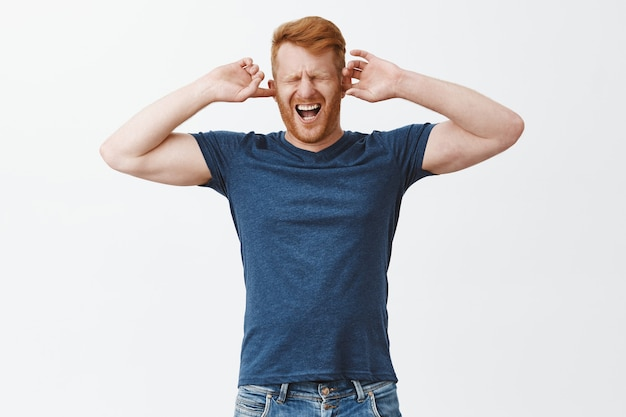 Displeased redhead guy feeling pain in head cause of noisy annoying sound, covering ears with fingers, shouting from painful feeling, closing eyes and yelling with opened mouth over grey wall