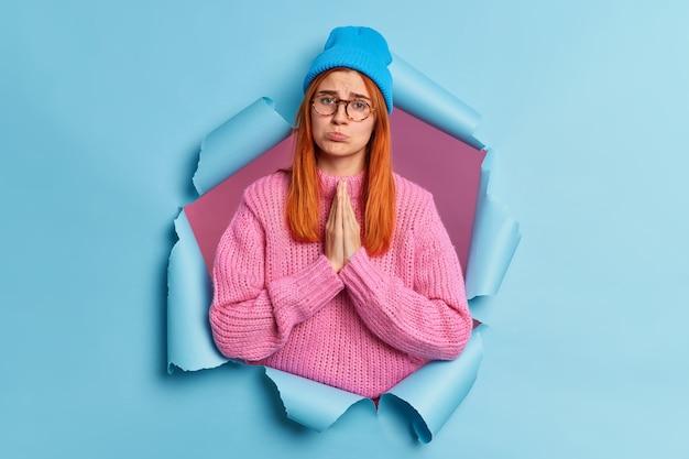 불쾌한 빨간 머리 여자는 손바닥을 함께 눌러 애원하는 얼굴 표정으로 호의를 요구합니다. 입술은 슬픈 표정이 파란색 모자와 니트 스웨터를 입었습니다.