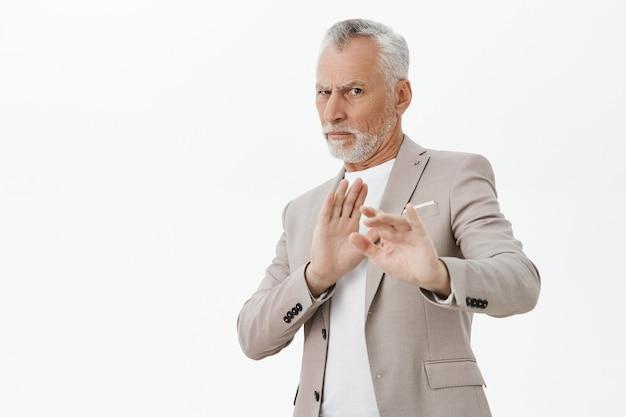 Uomo anziano dispiaciuto e riluttante alzando le mani ferma il gesto, rifiutando l'offerta, sfondo bianco