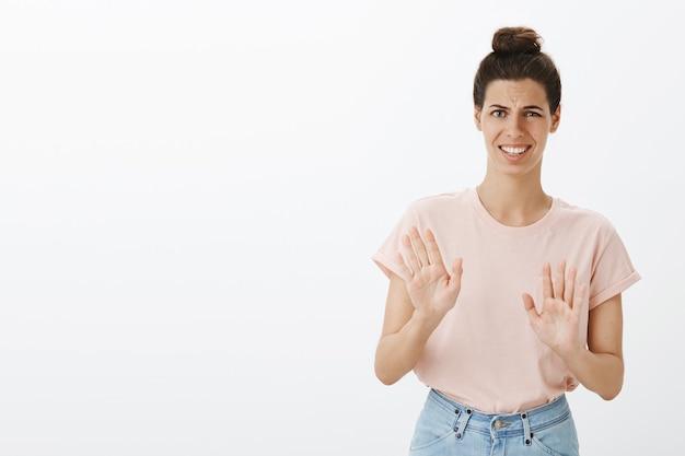 Giovane donna alla moda scontenta e riluttante che posa contro il muro bianco