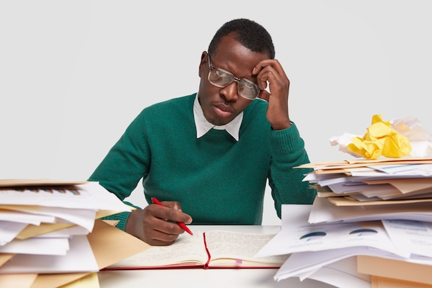 Недовольный грустный афро-американский рабочий-мужчина недоволен, устал от работы на рабочем месте, пишет информацию в блокноте