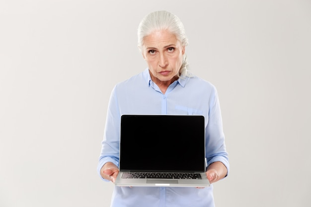 Displeased sad woman holding laptop computer with blank screen