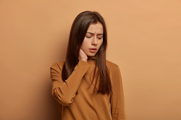 Displeased sad woman touches neck, looks down with unhappy expression, thinks about her problems with worried look, wears brown jumper