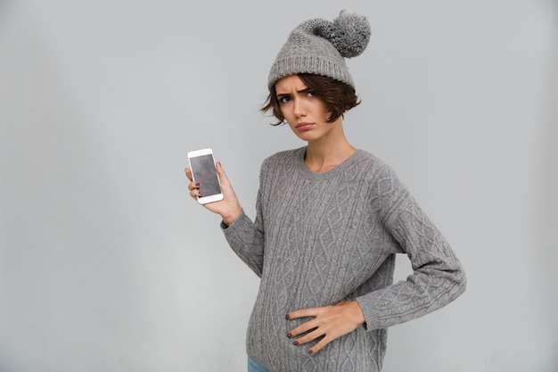 Displeased sad young woman showing display of mobile phone.