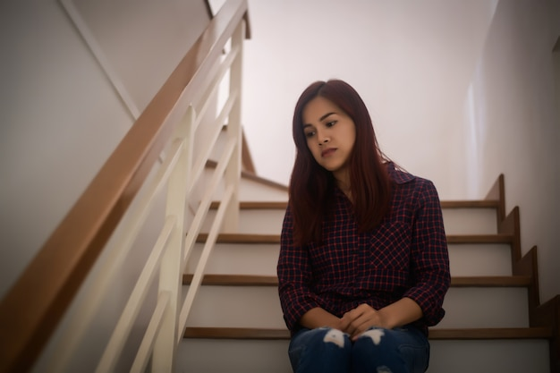 Displeased sad young woman sitting on stairs.