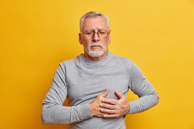 Displeased senior man presses hand to chest has heart attack needs pinkillers dressed in casual turtleneck wears spectacles isolated over yellow wall