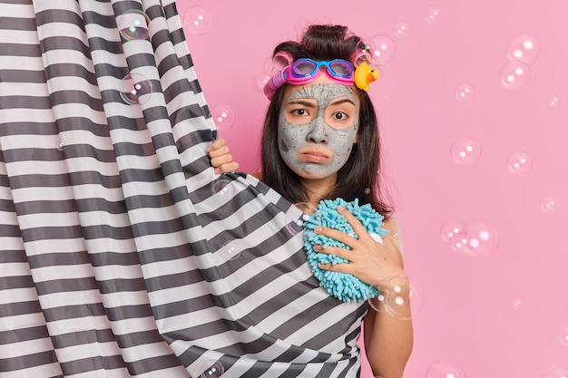 Displeased serious asian woman looks directly at camera hides behind shower curtain undergoes beauty procedures in douche applies clay facial mask poses against pink background with bubbles around
