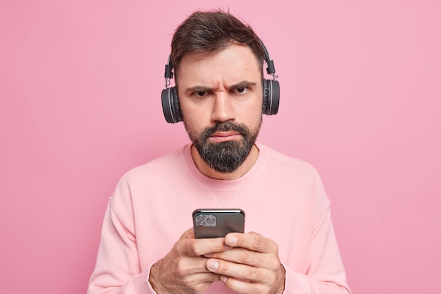불쾌한 심각한 수염 난 남자는 스테레오 헤드폰을 착용하고 휴대 전화 다운로드 노래를 재생 목록에 보유하고 엄격한 표현을 가지고 분홍색 벽에 부담없이 포즈를 취합니다. 기술 개념