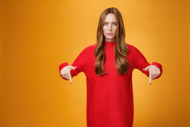 Недовольная серьезная женщина в вязаном красном платье, нахмурившись, озабоченно смотрит на неприятную неуместную вещь, разочарованную и несчастную, стоящую на оранжевом фоне