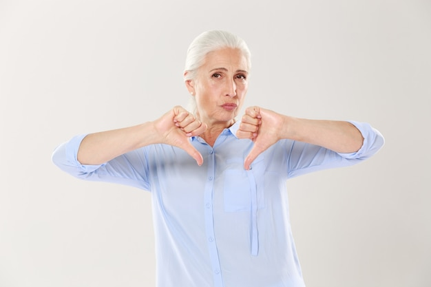 Displeased serious old woman showing thumb down