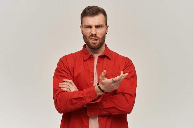 Il giovane scettico scontento in camicia rossa con la barba tiene le braccia incrociate e tiene il copyspace sul palmo sopra il muro bianco