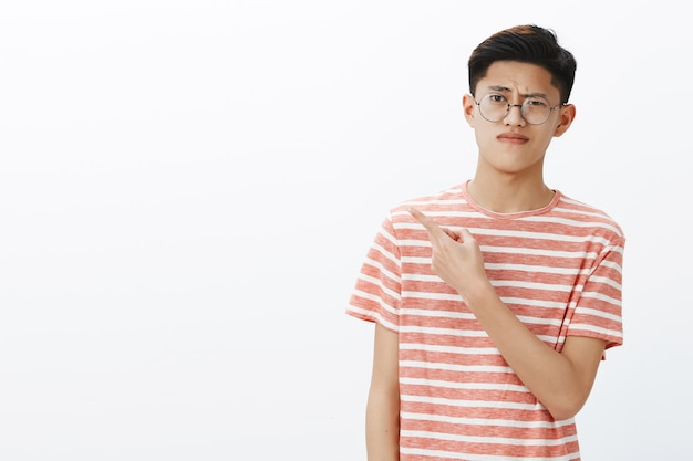 Displeased smart young attractive asian male student in glasses and t-shirt raising eyebrow in scorn and doubt pursing lips from dislike pointing backwards or left questioned