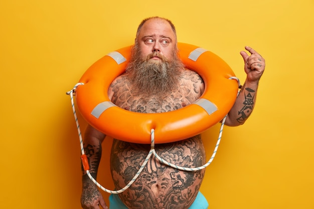 Displeased stout man has thick beard and big belly, tattoos, shows very little size gesture, poses with inflated lifebuoy, demonstrates small size of something, isolated on yellow wall