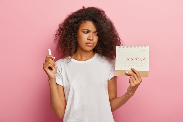 不機嫌なストレスの多い暗い肌の女性は、マークされた赤い十字で生理カレンダーを見る