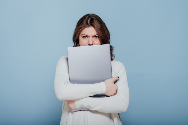 불쾌한 세련된 여성 인상을 찌푸리고 파란색 배경에 격리된 노트북을 껴안고 카메라를 바라보고 있습니다.
