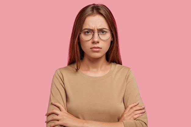 La femmina imbronciata dispiaciuta ha un'espressione scontenta, tiene le mani incrociate, mostra la sua antipatia, aggrotta le sopracciglia, si sente infelice, ha i capelli scuri dritti, posa contro il muro rosa. concetto di emozioni negative