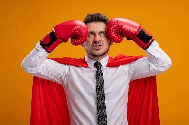赤いマントとボクシンググローブで頭を殴り、オレンジ色の壁の上に顔をしかめる不機嫌なスーパーヒーローのビジネスマン