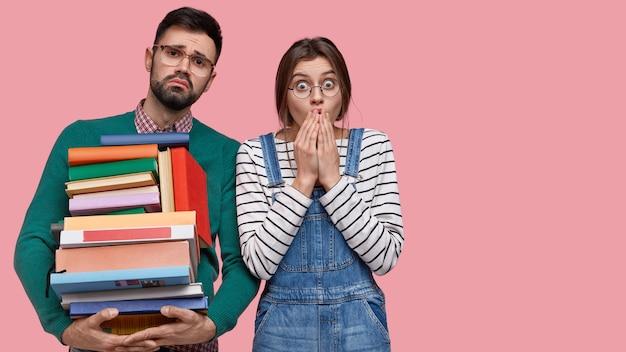 Giovane donna e uomo scontenti e sorpresi, tengono in mano libri di testo, stanno vicini l'uno all'altro