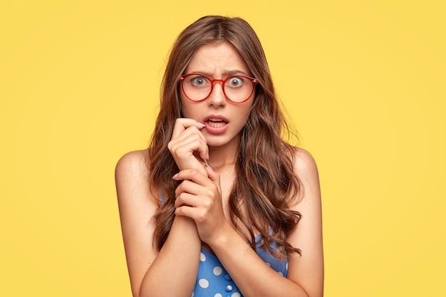 黄色い壁に向かってポーズをとっている眼鏡で不機嫌な驚きの若い女性