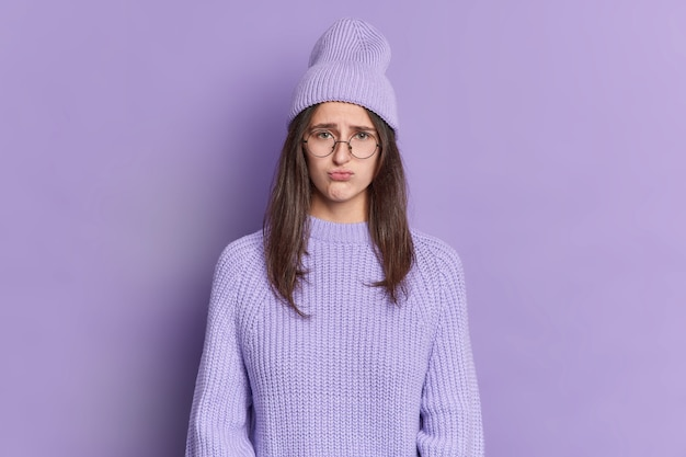 Displeased teenage girl has sulking gloomy expression purses lips looks offended wears big round spectacles hat and jumper.