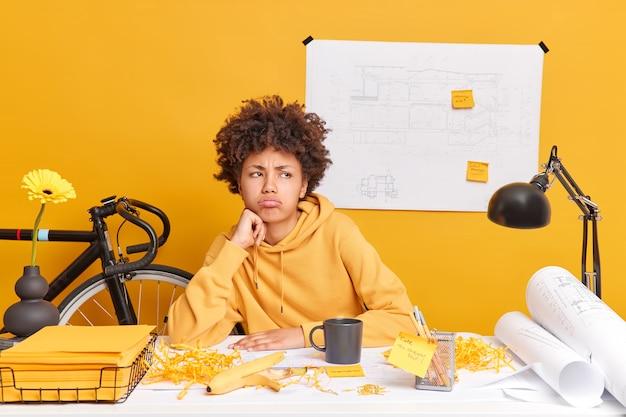 불쾌한 사려 깊은 아프리카 계 미국인 여성이 prject에서 열심히 일하고 있습니다.