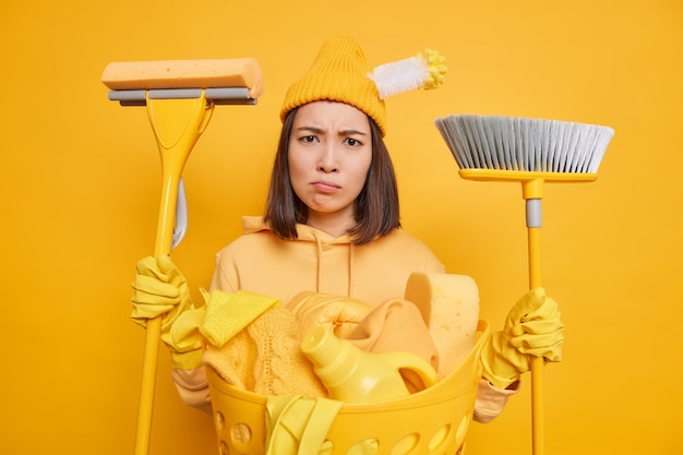 Displeased tired asian woman frowns face has no desire to clean house holds mop and broom busy doing laundry wears protective rubber gloves hat and sweatshirt isolated over yellow background