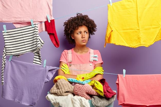 不機嫌な疲れた主婦は顔を向け、洗面台の近くで腕を組んで洗濯物を持って立ち、家で洗濯をするのに忙しく、洗濯物をきれいな洗濯物で近くに置き、家の雑用をします。