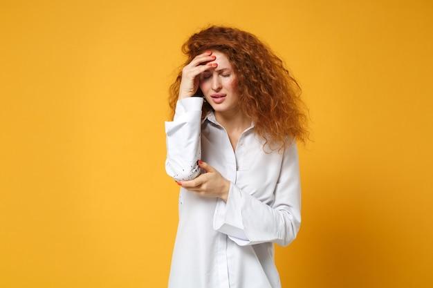 黄色いオレンジ色の壁に孤立したポーズをとってカジュアルな白いシャツを着た不機嫌な疲れた若い赤毛の女性の女の子
