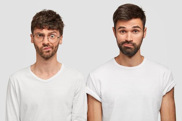 Due uomini dispiaciuti si accigliano in volto per lo scontento, hanno espressioni perplesse, vestiti in modo casual, hanno grosse stoppie