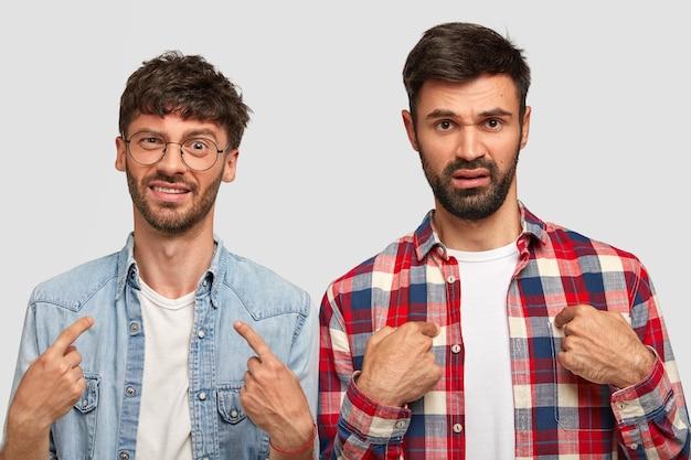 Два недовольных молодых человека указывают на себя, спрашивают, почему они должны выполнять обязанности по дому, недовольно хмурятся, носят стильные рубашки, имеют темную щетину, изолированы на белой стене