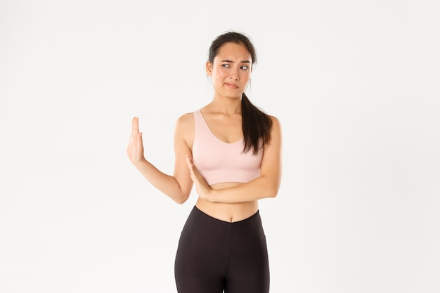 Displeased and unamused asian fitness girl showing block with hand and looking left disgusted, express aversion and reject something bad.