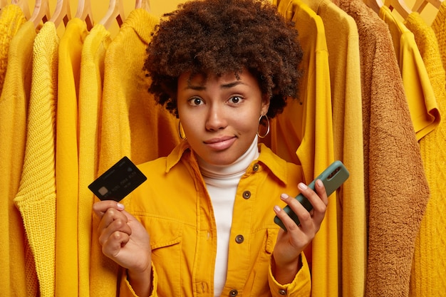Displeased unaware woman with curly hairstyle, unable to pay all sum of money for clothes, holds plastic card and modern mobile phone, poses against plain yellow jumpers on hangers.