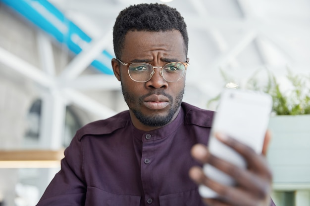 Displeased unhappy dark skinned male office manager looks with upset expression at smart phone, recieves message with bad news