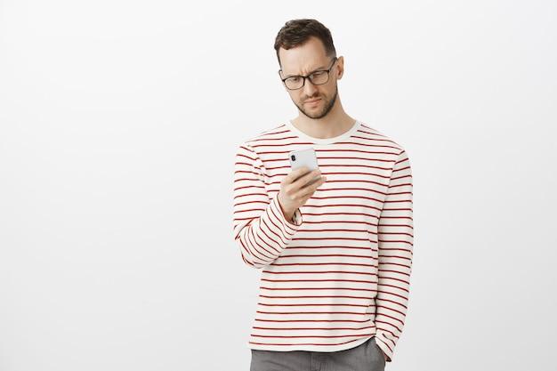 ストライプの衣装とメガネで不機嫌なハンサムな男性モデル、スマートフォンを保持している、嫌いから画面で眉をひそめている