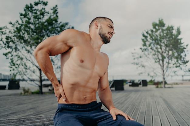 Недовольный небритый европейский спортсмен трогает поясницу и чувствует боль в спине после физических упражнений, позирует на улице.