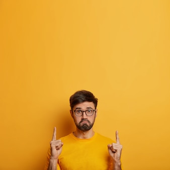 Displeased unshaven man purses lips, looks unhappily , feels insulted, demonstrates copy space for product or service promo, dissatisfied with no discounts in shop, poses over yellow wall Free Photo