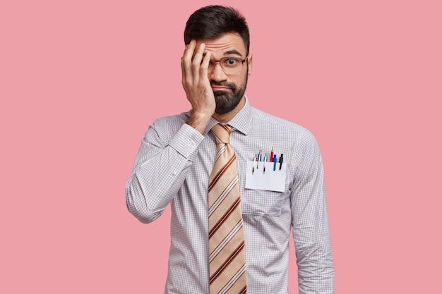 不機嫌な無精ひげを生やした若い男は恥ずかしがり屋の表情をしており、手で顔を覆い、大きな光学メガネ、フォーマルシャツを着て、驚いた視線を持って、ピンクの空間に孤立しています
