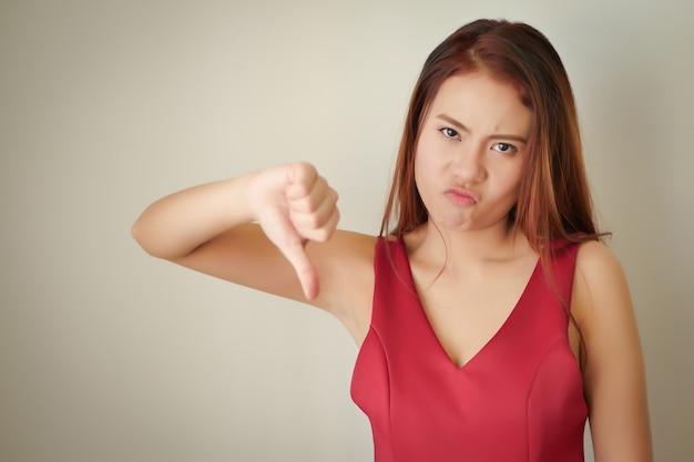 불쾌한 화가 화가 인상을 찌푸리고 엄지손가락을 아래로 제스처를 주는 여자, 아시아 여성 모델