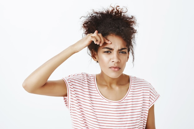 Displeased upset woman with afro hairstyle posing in the studio