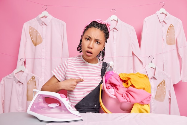 Displeased woman asks why i should do all housework points at herself carries bucket of laundry has indignant expression stands near ironing board uses electric steam iron dressed in casual clothes