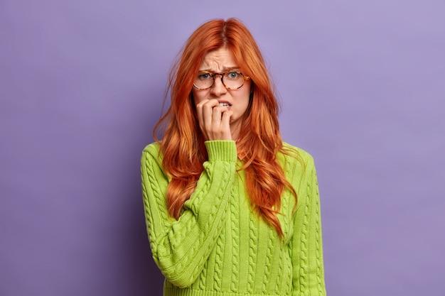 不機嫌な女性が指の爪を噛むと顔が眉をひそめ、何かが原因で不幸にも緊張しているように見えます。