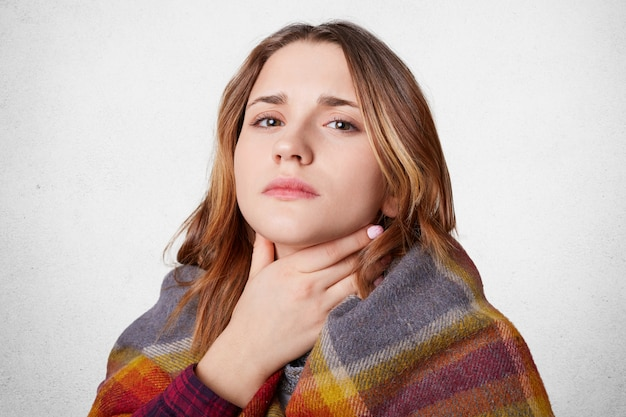 Displeased woman covered with warm blanket
