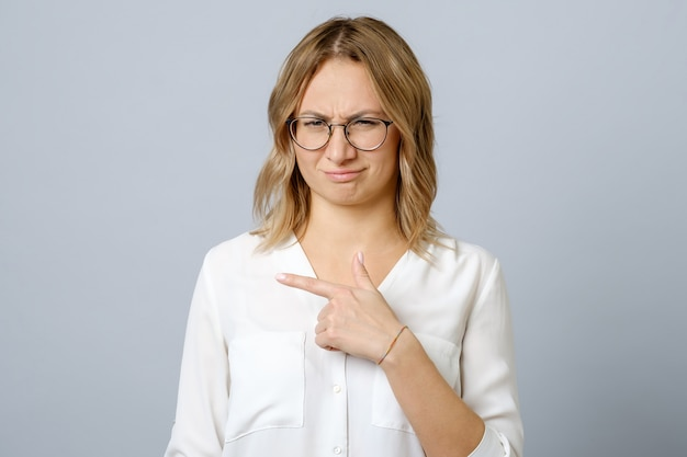 Displeased woman in glasses pointing left with dislike