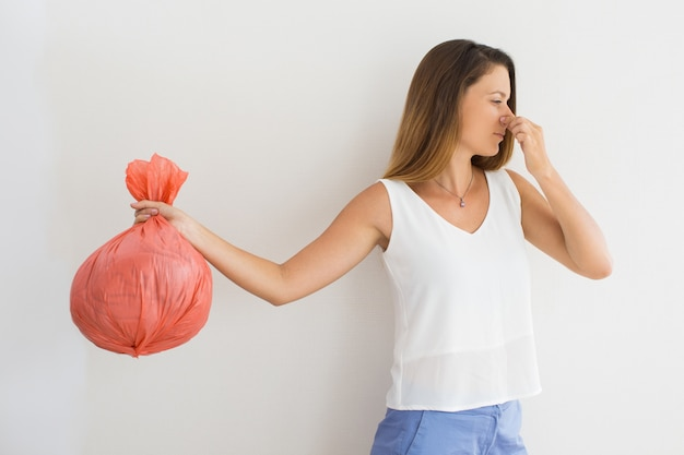 Displeased woman holding garbage bag