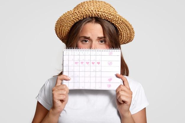 Недовольная женщина держит календарь периодов