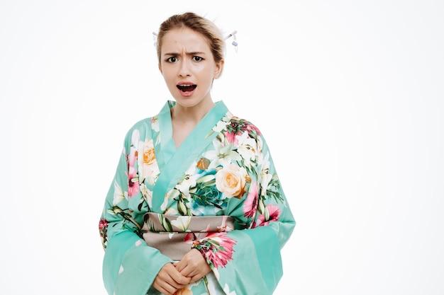 白に怒ってがっかりしている伝統的な日本の着物の不機嫌な女性