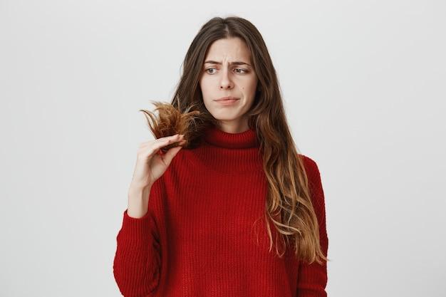 Недовольная женщина смотрит на секущиеся волосы