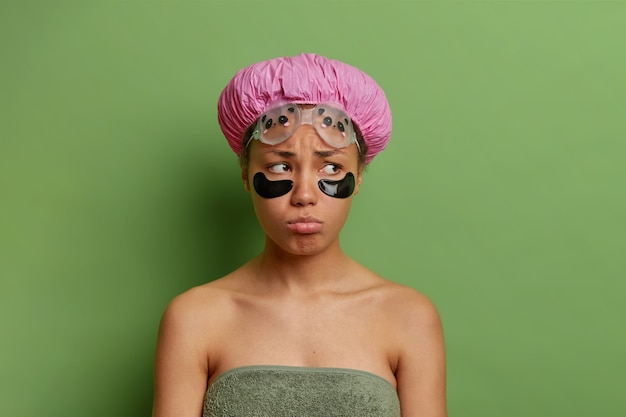 Displeased woman looks with gloomy expression undergoes beauty procedures after taking shower wrapped in towel wears bath hat isolated over green wall
